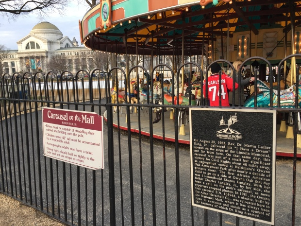 The historical marker on the carousel on the Mall.
